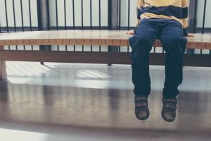 Rintakehästä alaspäin kuvattu lapsi, joka istuu penkillä.